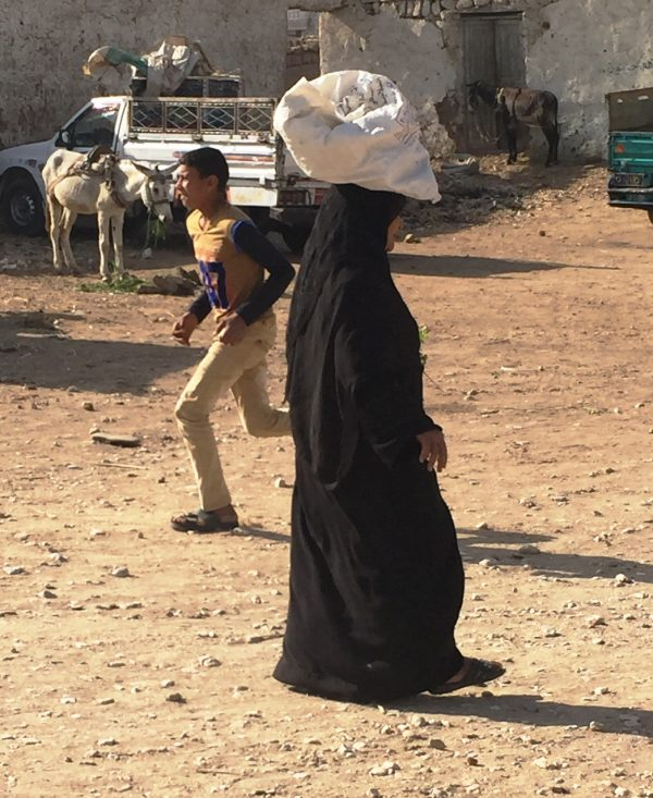 Woman carrying goods on her head in Egypt